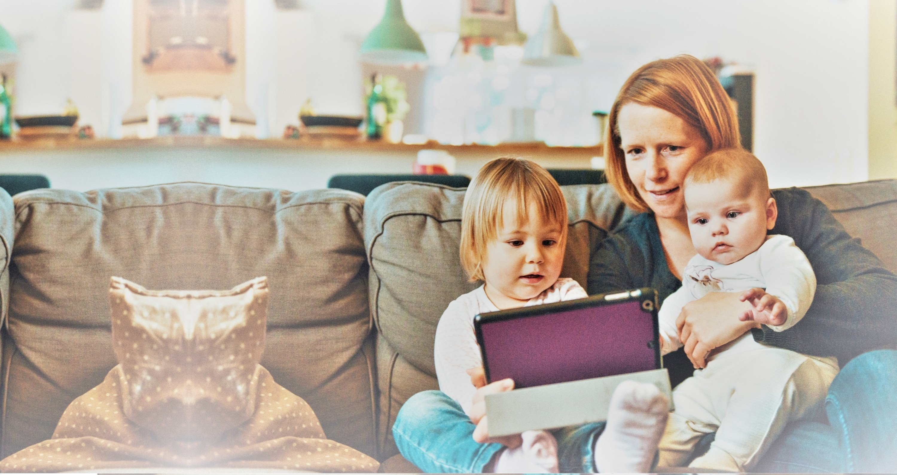 woman and children on couch looking at tablet